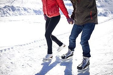 Caucasian couple ice skating on snowy frozen lake