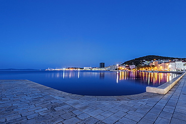 Waterfront sidewalk, illuminated boats and dock at dusk, Split, Split, Croatia