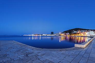 Waterfront sidewalk, illuminated boats and dock at dusk, Split, Split, Croatia