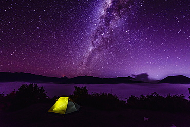 Milky Way galaxy over campsite in starry night sky
