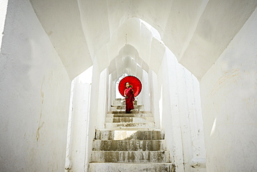 Asian monk under umbrella on temple staircase, Mingun, Mandala, Myanmar