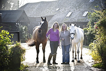 Two women standing outside a stable with two horses, England