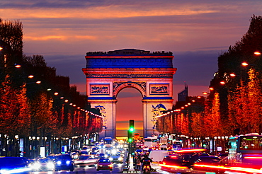 Arc de Triomphe over traffic at night, Paris, Ile-de-France, France