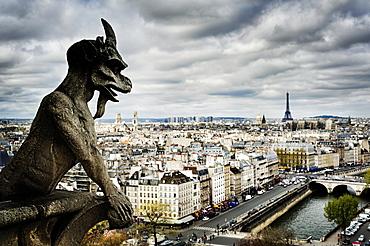 Gargoyle sculpture over Paris cityscape, Ile-de-France, France