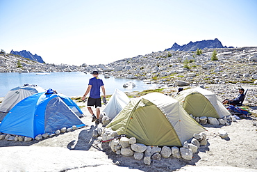 Man walking by tents at campsite in desert landscape, Leavenworth, Washington, USA