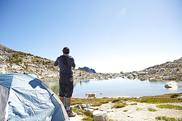 Man standing at tent at campsite near rural lake, Leavenworth, Washington, USA