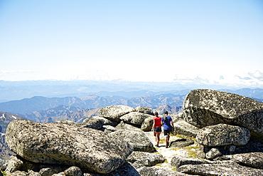 Couple hiking on rocky hilltop, Leavenworth, Washington, USA