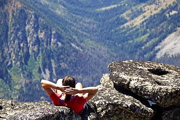 Hiker sitting on rocky hilltop, Leavenworth, Washington, USA