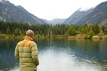 Hiker admiring lake and remote landscape, North Bend, Washington, USA