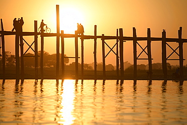 People walking on elevated wooden walkway at sunset, Myanmar, Burma