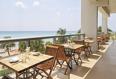 Empty tables on restaurant balcony, Miami, Florida, USA