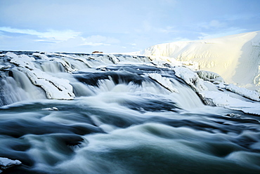 Time lapse view of river flowing over icy rock formations, Gullfoss, Iceland
