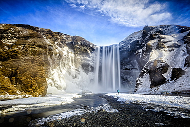 Waterfall pouring over icy cliffs in remote landscape, Skogafoss, Iceland