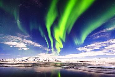 Northern lights reflecting in still remote river, Jokulsarlon, Iceland