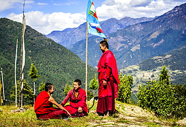 Asian monks with flag on remote hilltop, Bhutan, Kingdom of Bhutan