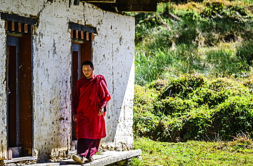 Asian monk walking by monastery doors, Bhutan, Kingdom of Bhutan