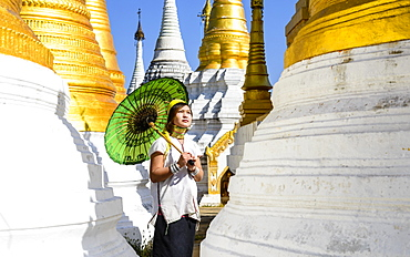 Asian woman carrying parasol at temple, Mingun, Mingun, Myanmar