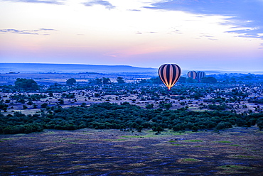 Hot air balloon flying over savanna landscape, Kenya, Africa