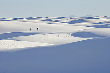 Distant people walking on snowy landscape, White Sands National Monument, New Mexico, USA