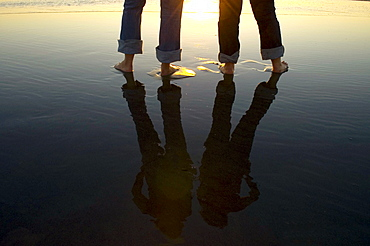 Reflection of legs in water at beach, Ventura, California, USA