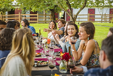 Friends enjoying wine at party outdoors, Langly, Washington, USA