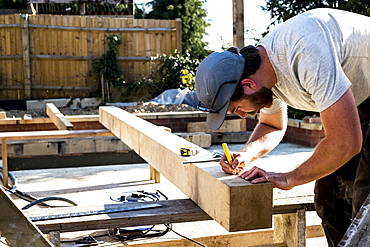 Man wearing baseball cap standing on building site, measuring and marking wooden beam, Oxfordshire, England
