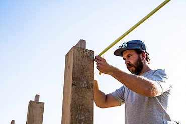 Man wearing baseball cap and sunglasses on building site, using tape measure, Oxfordshire, England