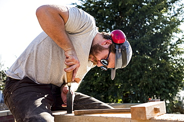 Man wearing baseball cap, sunglasses and ear protectors on building site, working on wooden beam, Oxfordshire, England