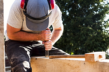 Man wearing baseball cap and ear protectors on building site, working on wooden beam, Oxfordshire, England