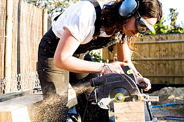 Woman wearing protective goggles and ear protectors holding circular saw, cutting piece of wood on building side, Oxfordshire, England
