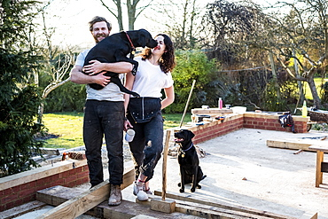 Smiling man and women and two black dogs on building site of residential building, Oxfordshire, England