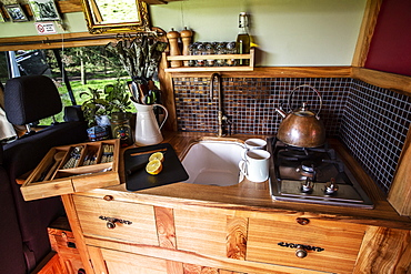 Interior view of camper van with small cooking area and sink, Oxfordshire, England