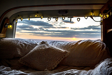 Camper van with cushion and fairy lights, view through rear window at sunset, Oxfordshire, England