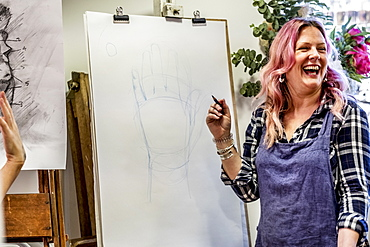 Laughing woman wearing apron standing at an easel, drawing of human hand, Oxfordshire, England