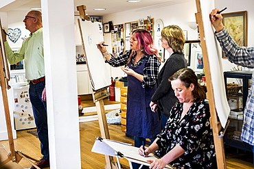 Group of artists standing and sitting at easels, drawing, Oxfordshire, England