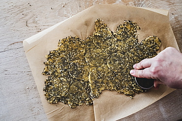 High angle close up of person cutting discs of seeded cracker dough, England