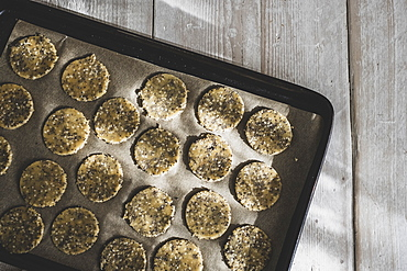 High angle close up of seeded cracker dough on a baking tray, England