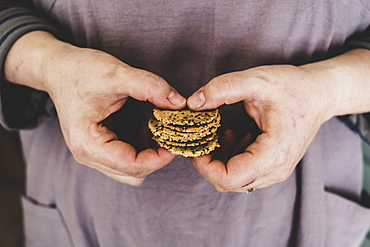 Close up of person holding small stack of freshly baked seeded crackers, England
