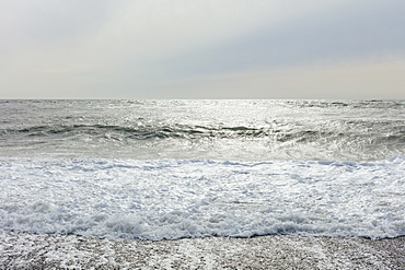 The surface of the ocean and waves, moody overcast sky above, Washington, USA