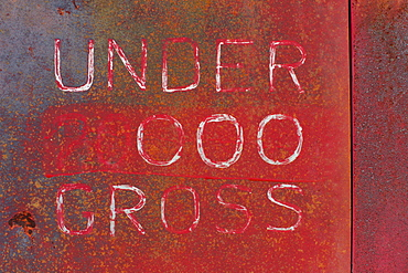 """Under 000 Gross"" painted on side of old truck door, Whitman County, Washington, USA"