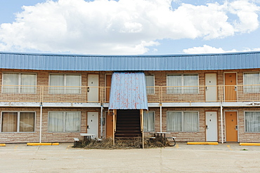 Abandoned motel building with a rusty metal awning, drawn curtains at the windows, and tumbleweed around the steps, Kansas, United States