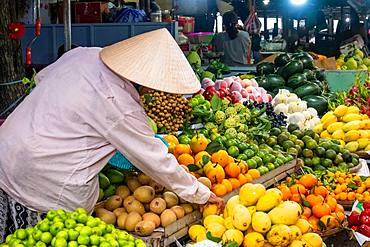 Vendor at his fruit and vegetable stall at a market in Hoi An, Vietnam