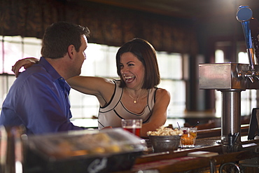 A man and woman seated at a bar, flirting and talking. On a date, New Hope, Pennsylvania, USA