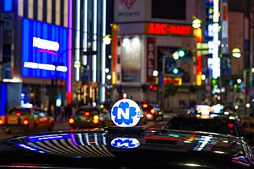 Roof of taxi and neon advertising signs at night in Shinjuku District, Tokyo, Japan