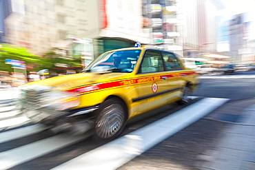 TOKYO, JAPAN ヨ JUNE 06 2015: Motion blurred yellow taxi cab on pedestrian crossing, Tokyo, Japan
