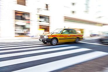 Motion blurred shot of yellow taxi cab on pedestrian crossing, Tokyo, Japan