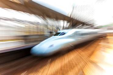 Blurred motion view of Shinkansen Bullet Train at the platform of Tokyo Station, Japan