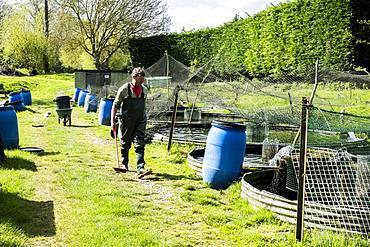 Man wearing waders walking past water tanks at a fish farm raising trout