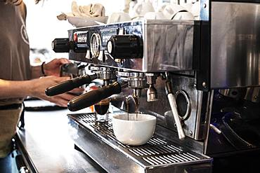 Close up of person making a cappuccino using commercial espresso machine
