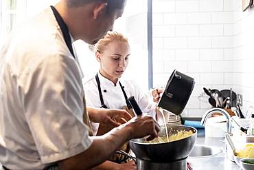 Male and female chef wearing brown aprons standing at kitchen counter, making Hollandaise Sauce